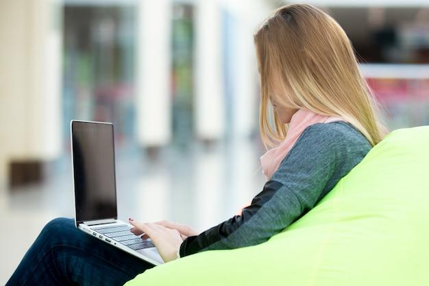 Typage fille sur un ordinateur portable Photo gratuit