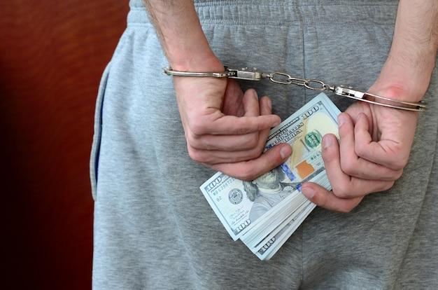Un type arrêté en pantalon gris aux mains menottées détient une énorme quantité de billets d'un dollar. vue arrière Photo Premium