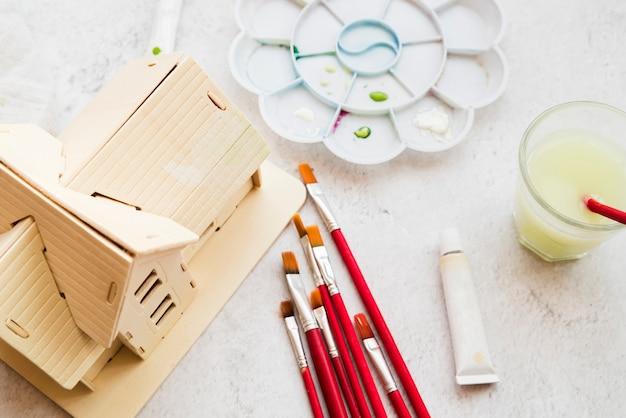 Type de pinceau différent; modèle de maison et palette de couleurs et tube de peinture acrylique sur fond texturé blanc Photo gratuit