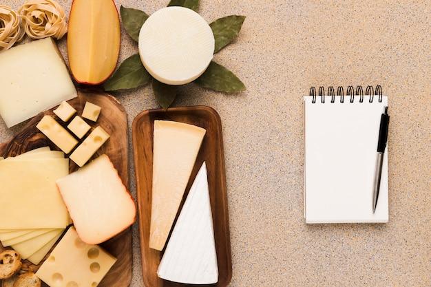 Types de fromages sains sur une plaque en bois avec bloc-notes et stylo blancs vierges Photo gratuit