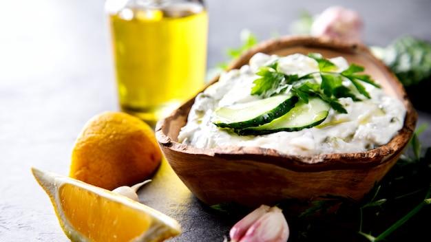 Tzatziki sauce grecque traditionnelle avec des ingrédients concombre, ail, persil, citron, menthe. Photo Premium