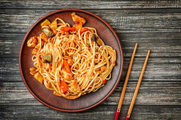 Udon sauté nouilles au poulet et sauce aigre-douce et des bâtons en bois sur la table en bois Photo Premium