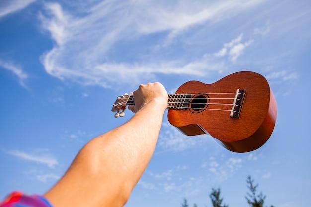 Ukulele Guitare étant Tenue Dans Les Airs Photo gratuit