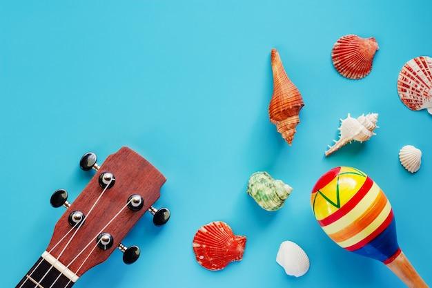 Ukulélé, maracas et coquillages sur fond bleu Photo Premium