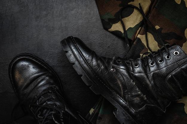 Uniforme de camouflage militaire et des bottes. un ensemble d'éléments de pistolet de flasque militaire sur un fond sombre Photo Premium