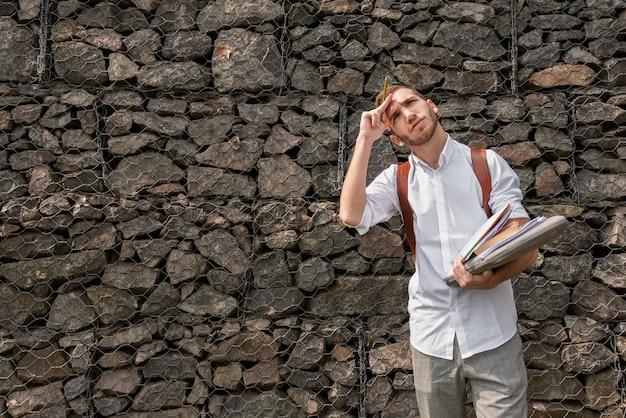 Université étudiant tenant des dossiers de livres et de notes et levant les yeux Photo gratuit