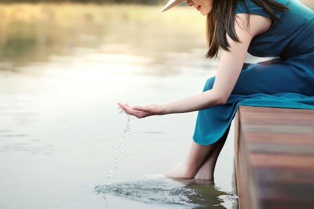 Unplugged life ou human living avec nature concept. heureuse jeune femme relaxante au bord du fleuve Photo Premium