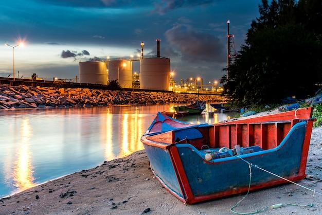 Usine industrielle de raffinerie de pétrole et de gaz avec rivière naturelle et bateau. Photo Premium