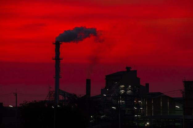 L'usine a libéré une cheminée de fumée au coucher du soleil Photo Premium