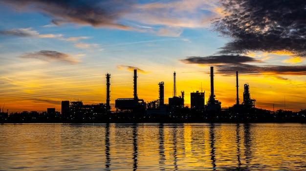Usine de raffinage de pétrole et de gaz avec éclairage scintillant et lever du soleil le matin Photo Premium