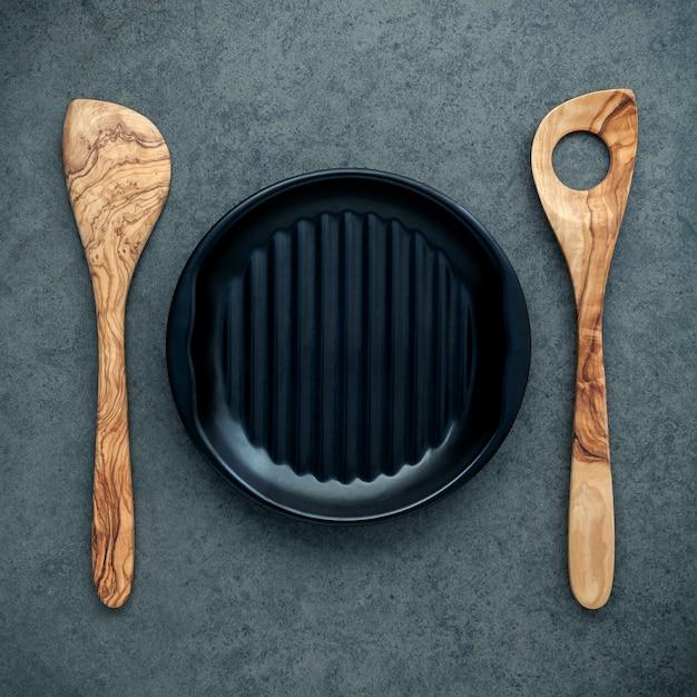 Ustensiles de cuisine en bois, cuillères en bois, spatule et plaque noire sur fond sombre. Photo Premium