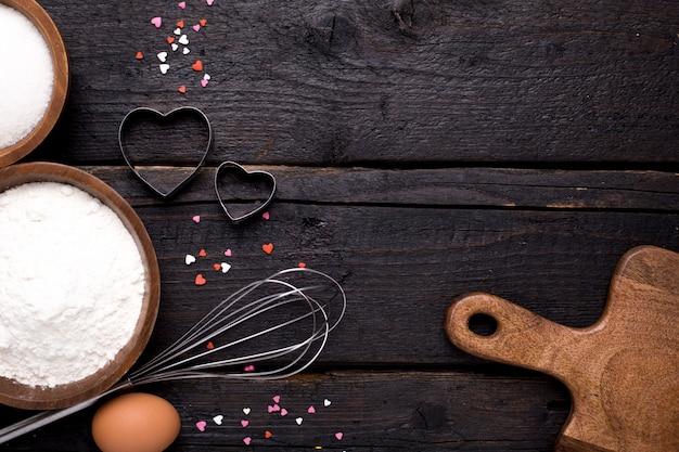 Ustensiles de cuisine, farine et sucre sur bois Photo Premium