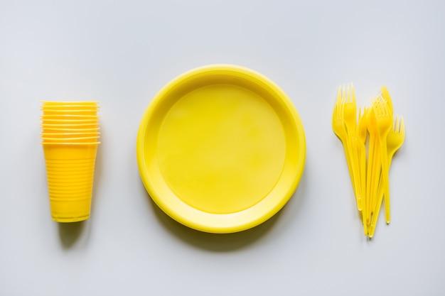 Ustensiles jaunes de pique-nique à usage unique, assiettes, tasses, fourchettes sur fond gris. Photo Premium