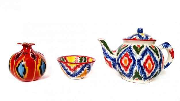 Ustensiles traditionnels ouzbeks - bouilloire, bol, grenade avec ornement ikat sur blanc, isolé Photo Premium