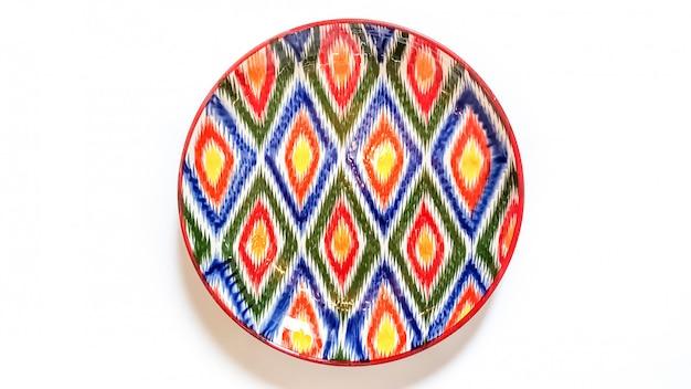 Ustensiles traditionnels ouzbeks - plaque avec ornement ikat sur blanc, isolé Photo Premium