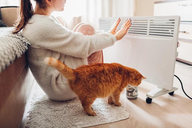 Utilisation de chauffage à la maison en hiver. femme réchauffant ses mains avec un chat. saison de chauffage. Photo Premium