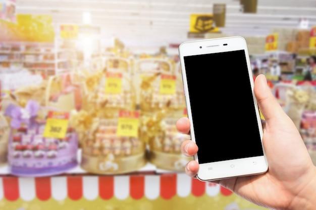 Utilisation féminine tenir smartphone images floues de nombreux nid d'oiseau comestible soit paniers-cadeaux boissons sains à vendre au supermarché Photo Premium