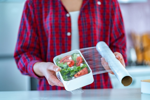 Utilisation D'un Film Plastique En Polyéthylène Alimentaire Pour Le Stockage Des Aliments Dans Le Réfrigérateur à La Maison Photo Premium