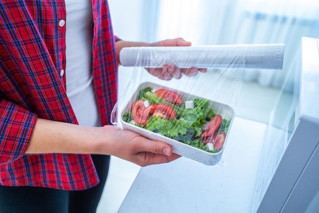 Utilisation D'un Film Plastique En Polyéthylène Alimentaire Pour Le Stockage Des Aliments Dans Le Réfrigérateur Photo Premium