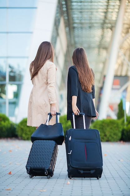 Vacances. deux élégantes voyageurs marchant avec leurs bagages à l'aéroport Photo Premium