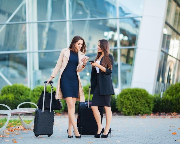 Vacances, Deux Filles Heureuse Voyageant à L'étranger Ensemble, Transportant Une Valise à L'aéroport Photo Premium