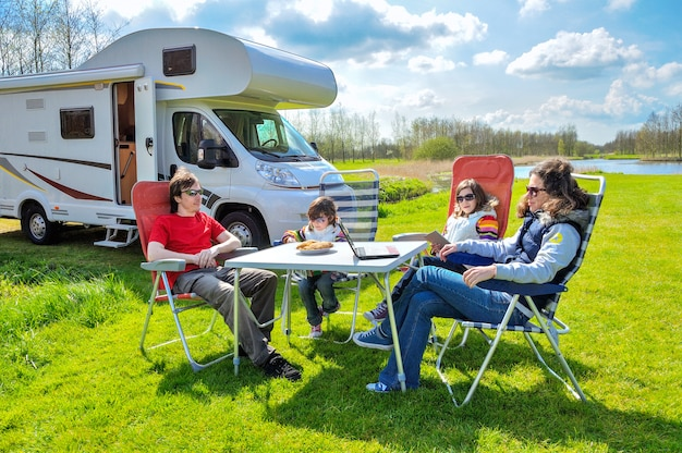Vacances En Famille, Voyage En Camping-car Avec Des Enfants, Parents Heureux Avec Des Enfants Assis à La Table En Camping En Voyage De Vacances En Camping-car Photo Premium