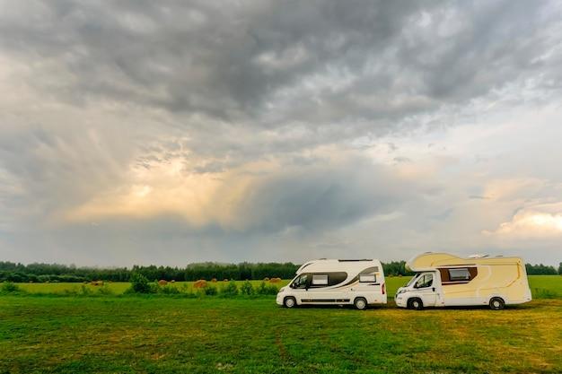 Vacances En Famille Et Voyages (voyage) à L'extérieur En Camping-car (caravane). Deux Camping-cars Dans Un Camp D'été à L'extérieur. Voyage (voyage) En Concept De Voiture. Photo Premium