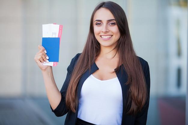 Vacances. une femme près de l'aéroport est titulaire d'un billet d'avion et d'un passeport Photo Premium