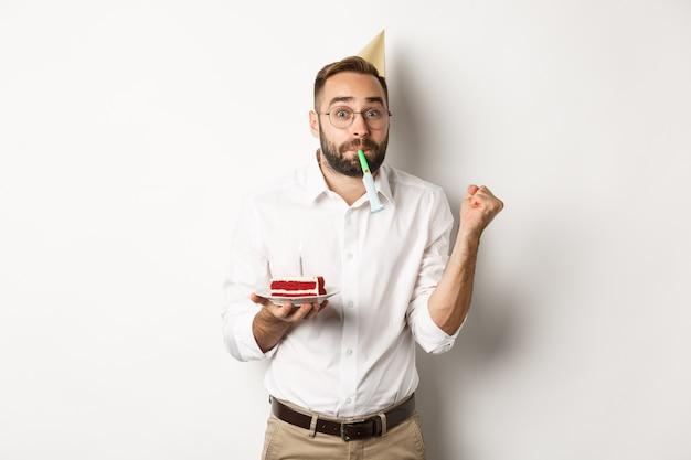 Vacances Et Fête. Joyeux Homme Appréciant L'anniversaire, Soufflant Un Sifflet De Fête Et Tenant Un Gâteau Bday Photo gratuit