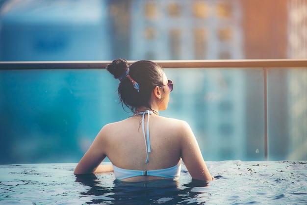 Vacances à kuala-lumpur. jeune femme profiter de nager dans la piscine sur le toit avec vue magnifique sur la ville Photo Premium