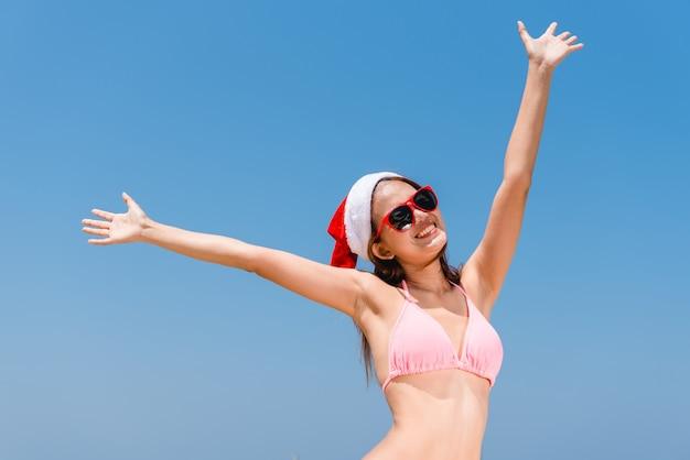 Vacances de noël vacances amusantes de plage bikini femme asiatique courir insouciant des éclaboussures d'eau profitant de la liberté de nager escapade de paradis de voyage des caraïbes avec noël santa hat. modèle de corps sexy. Photo Premium