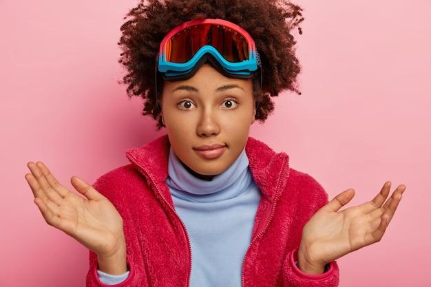Vacancier Désemparé, étend Les Paumes Avec Hésitation, Porte Un Masque De Ski Sur La Tête, Vêtements Décontractés, Pose à L'intérieur Photo gratuit