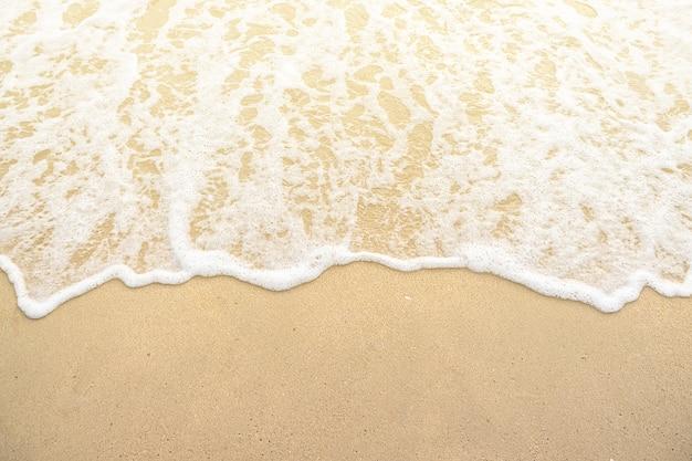 Vague douce sur le coucher de soleil sur la plage de sable Photo Premium