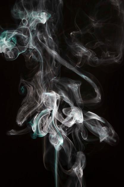 Vagues de fumée violettes blanches et turquoises isolées sur fond noir Photo gratuit