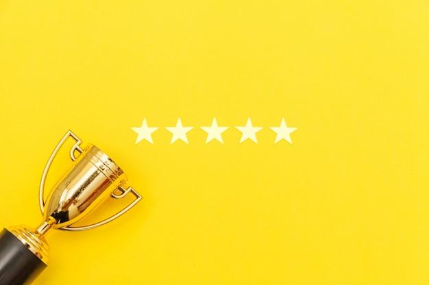 Vainqueur De La Conception Simplement Plate Ou Champion Du Trophée D'or Et Coupe 5 étoiles Isolé Sur Fond Pastel Rose. Victoire Première Place De La Compétition. Concept Gagnant Ou Succès. Espace De Copie Vue De Dessus. Photo Premium