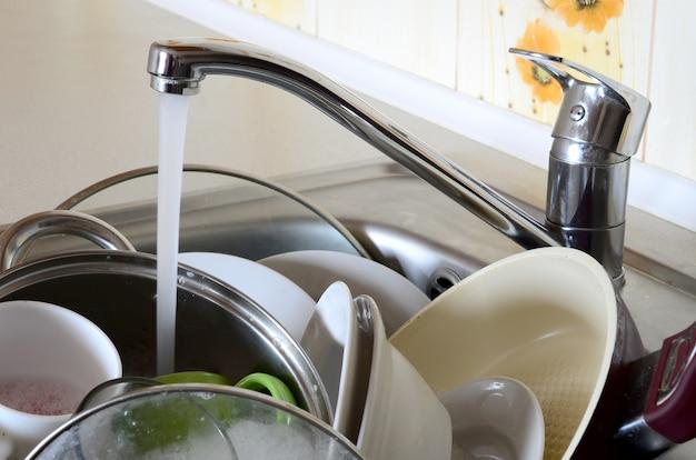 La vaisselle sale et les appareils de cuisine non lavés gisent dans l'eau mousseuse Photo Premium