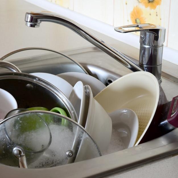 La vaisselle sale et les appareils de cuisine non lavés ont rempli l'évier de la cuisine Photo Premium