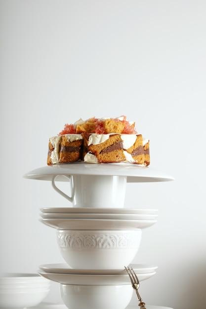 Vaisselle Vintage Blanche Et Cuillère à Dessert En Argent Avec Un Gâteau De Mariage Non Traditionnel Avec Du Chocolat, De La Crème Et Des Fruits Sur Le Dessus Photo gratuit