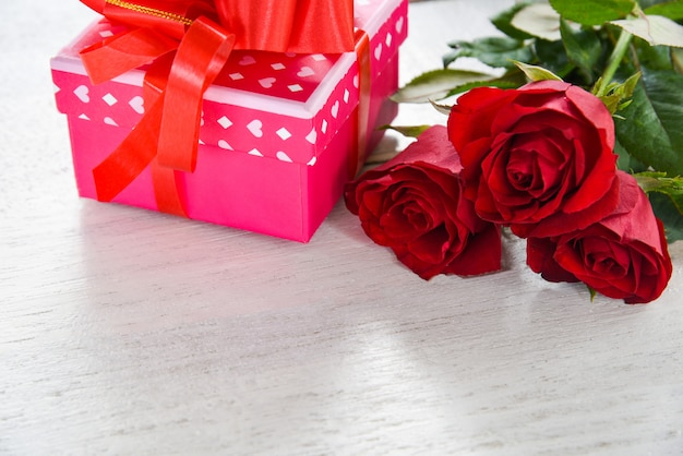 Valentin cadeau boîte fleur amour concept rose boîte de cadeau avec ruban noeud rose rouge fleurs sur bois blanc Photo Premium