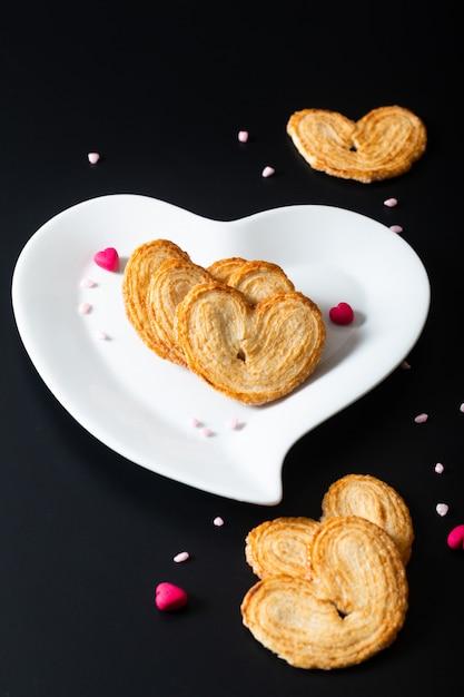 Valentine Dessert Food Concept Puff Pâtisserie Coeurs En Forme De Coeur En Céramique Blanche Sur Fond Noir Photo Premium