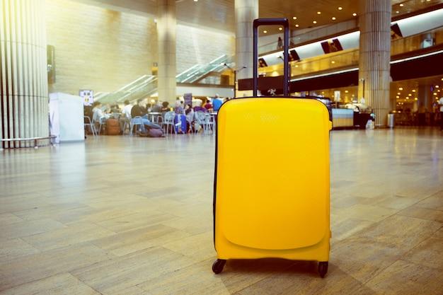 Valise Dans La Zone D'attente Du Terminal De L'aéroport Avec Une Zone Lounge En Arrière-plan. Concept De Thème De Vacances. Photo Premium