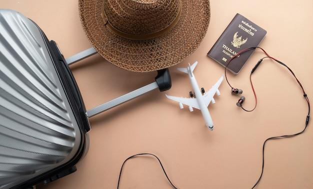 Valise plate gris avec chapeau marron et mini avion Photo Premium