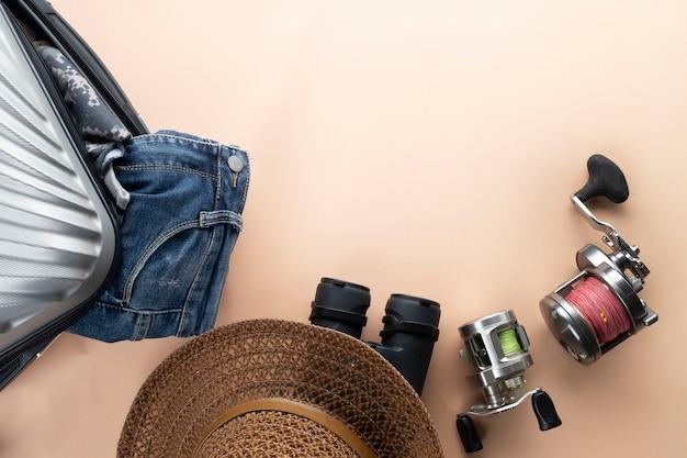 Valise plate grise avec jumelles, chapeau, jeans, filature pour la pêche et sandales. concept de voyage Photo Premium