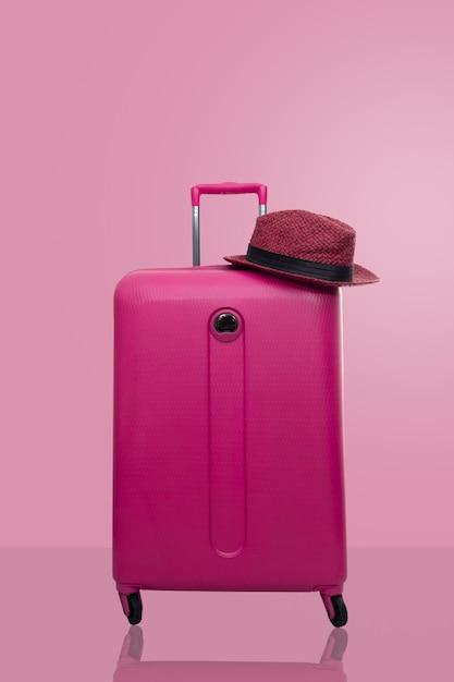 Valise rose avec un chapeau sur fond rose pastel. concept de voyage. Photo Premium