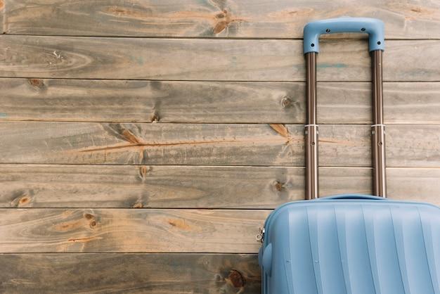 Valise de voyage bleue sur fond en bois Photo gratuit