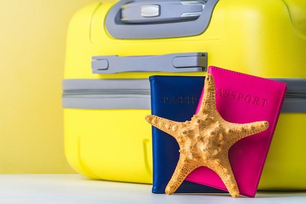 Une Valise De Voyage Jaune Vif, Un Passeport Et Une étoile De Mer. Concept De Voyage. Photo Premium