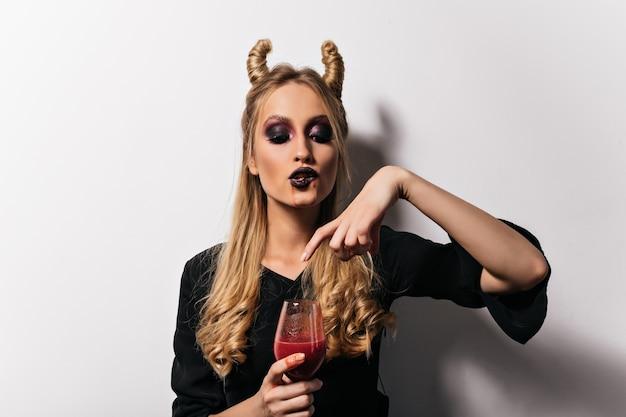 Vampire Femelle Buvant Du Sang De Verre à Vin. Belle Sorcière Blonde Appréciant La Poition à L'halloween. Photo gratuit