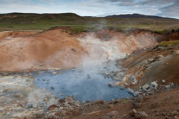 Vapeur sortant d'une piscine géothermique rocheuse Photo Premium