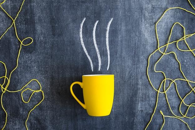 Vapeur tiré sur la tasse jaune avec du fil de laine jaune sur le tableau noir Photo gratuit