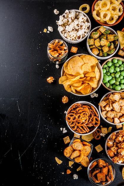 Variation différents craquelins malsains, maïs éclaté salé, tortillas, noix, pailles, bretsels Photo Premium